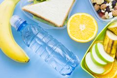 School lunch box. Bread, orange, bottle of water, baby corns, carrot and tomatoes in green plastic container. Top view, blue background stock photos