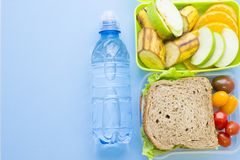 School lunch box. Bread, orange, bottle of water, baby corns, carrot and tomatoes in green plastic container. Top view, blue background royalty free stock images