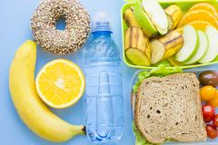 School lunch box. Bread, orange, bottle of water, baby corns, carrot and tomatoes in green plastic container. Top view, blue background royalty free stock image