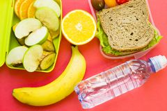 School lunch box. Bread, orange, bottle of water, baby corns, carrot and tomatoes in green plastic container. Top view, red background royalty free stock photography