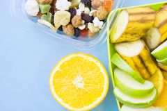 School lunch box. Bread, orange, candies, baby corns, carrot and tomatoes in green plastic container. Top view, blue background stock photography
