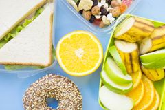 School lunch box. Bread, orange, candies, baby corns, carrot and tomatoes in green plastic container. Top view, blue background royalty free stock photos