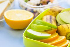School lunch box. Bread, orange, candies, baby corns, carrot and tomatoes in green plastic container. Top view, blue background stock photo