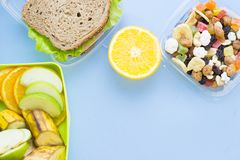 School lunch box. Bread, orange, candies, baby corns, carrot and tomatoes in green plastic container. Top view, blue background royalty free stock photography
