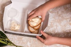 School lunch box for kids. Back to school. Child's hands. Top view, flat lay. School lunch box for kids. Back to school. Child's hands. White bread and butter in royalty free stock photo