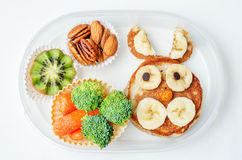 School lunch box for kids with food in the form of funny faces. The toning. selective focus royalty free stock image