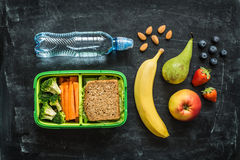 School lunch box with sandwich, vegetables, water and fruits. School lunch box with sandwich, vegetables, water, almonds and fruits on black chalkboard Stock Photography