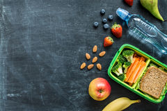 School lunch box with sandwich, vegetables, water and fruits. School lunch box with sandwich, vegetables, water, almonds and fruits on black chalkboard. Healthy Stock Images
