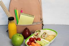School lunch box with sandwich, vegetables, water, fruits, backpack with school objects stock photography