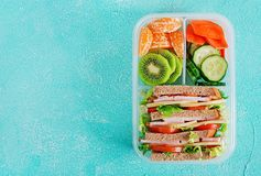 School lunch box with sandwich, vegetables, water, and fruits on table. Healthy eating habits concept. Flat lay. Top view stock photos
