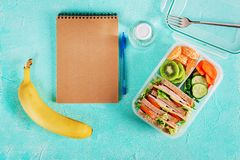 School lunch box with sandwich, vegetables, water, and fruits on table. Healthy eating habits concept. Flat lay. Top view stock photography