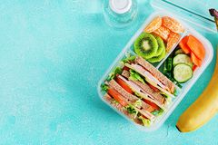 School lunch box with sandwich, vegetables, water, and fruits on table. Healthy eating habits concept. Flat lay. Top view stock photo