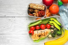School lunch boxes with chicken, avocado, eggs and fresh vegetables, bottle of water, nuts and fruits stock images