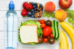 School lunch boxes with sandwich, fresh fruits and vegetables, berries and nuts and bottle of water Stock Image