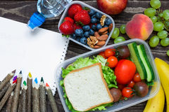 School lunch boxes with sandwich, fruits, vegetables and bottle of water with colored pencils and empty copybook Stock Images