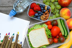 School lunch boxes with sandwich, fruits, vegetables and bottle of water with colored pencils royalty free stock image