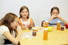 School Lunch in Cafeteria. A group of school children having lunch in the school cafeteria Stock Images