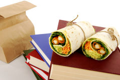 School lunch: chicken wrap sandwich with lunch bag, books on school desk Royalty Free Stock Photo