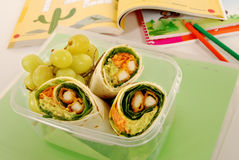 School lunch: chicken wrap sandwich in plastic box with books on school desk Royalty Free Stock Images