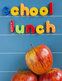 School lunch concept. School lunch text written in magnetic letter on a blue magnetic board. Three red tasty apples underneath the text. Healthy school lunch royalty free stock photo
