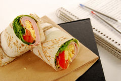 School lunch: ham and cheese wrap sandwich with lunch bag on the book Stock Photo