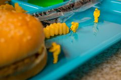 School Lunch Hazmat Health Inspection. Miniature hazmat team inspecting the nutritional value of unhealthy fast food school lunch royalty free stock images