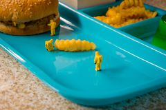 School Lunch Hazmat Health Inspection. Miniature hazmat team inspecting the nutritional value of unhealthy fast food school lunch royalty free stock image