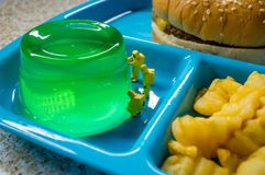 School Lunch Hazmat Health Inspection. Miniature hazmat team inspecting the nutritional value of unhealthy fast food school lunch royalty free stock photography