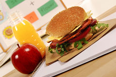 School lunch: pastrami roll sandwich, apple and drink on classroom desk Royalty Free Stock Photo