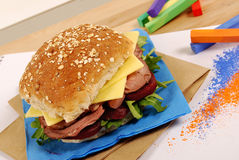 School lunch: roast beef and cheese roll sandwich on classroom desk Royalty Free Stock Image