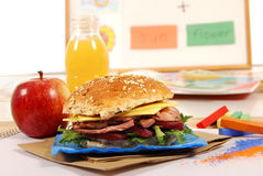 School lunch: roast beef roll sandwich, apple and drink on classroom desk Royalty Free Stock Photos