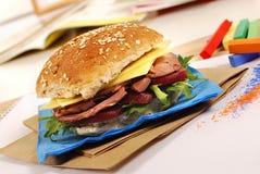 School lunch: roast beef roll sandwich with lunch bag on school desk Stock Photo