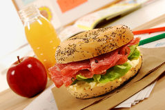 School lunch: salami bagel sandwich with apple and drink on classroom desk Stock Images