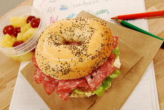School lunch: salami bagel sandwich with lunch bag on classroom desk Stock Images