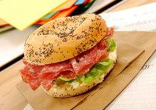 School lunch: salami bagel sandwich with lunch bag on classroom desk Royalty Free Stock Image