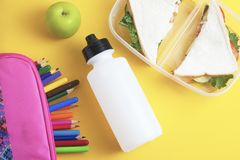 School lunch sandwich and green apple, bottle of water, healthy eating concept, colorfu encils yellow background, top view with co. School lunch sandwich and stock image