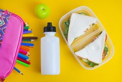 School lunch sandwich and green apple, bottle of water, healthy eating concept, colorfu encils yellow background, top view with co stock photo