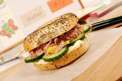 School lunch: tuna bagel sandwich on classroom desk with white board Stock Photo