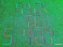 School material in composition on grass background royalty free stock images