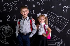 School mates, boy and girl, standing before the chalkboard as a background with a backpack on their backs. Disappointed. Girl holding her hand on the boy`s royalty free stock images
