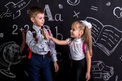 School mates standing before the chalkboard as a background with a backpack on their backs claping their hands looking. To each other. Boy and girl stock image