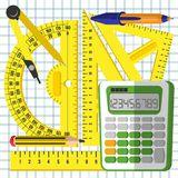 School mathematics kit. Measuring accessories and a calculator on the background of a sheet in a cage Royalty Free Stock Photo