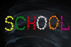School message from colorful letters on black background. School message from colorful letters on black chalkboard background stock photo