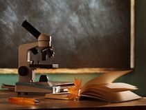 School microscope in classroom. On blackboard background royalty free stock images