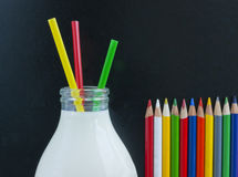 School milk concept. School milk. Milk bottle, three colourful plastic straws and set of crayons against traditional blackboard background. Give children the stock images