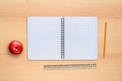School notebook, apple, pencil and ruler on desk Stock Photos