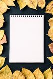 Spiral notebook on black background with autumn leaves, spiral o. School notebook on a black background with autumn leaves, spiral notepad on a table Royalty Free Stock Photo