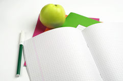 School notebook and felt-tip pens. Opened school notebook, felt-tip pens and green apple stock photography