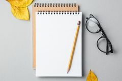 School notebook on a grey background with autumn leaves. Spiral notepad on a table Royalty Free Stock Image