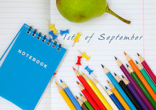 School notebook. Open school notebook for the first September with colored pencils, notebooks and stationery buttons royalty free stock photos